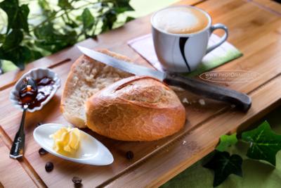 Food-Fotografie: knuspriges Frühstücksbrötchen mit Marmelade und heißem Cappuccino
